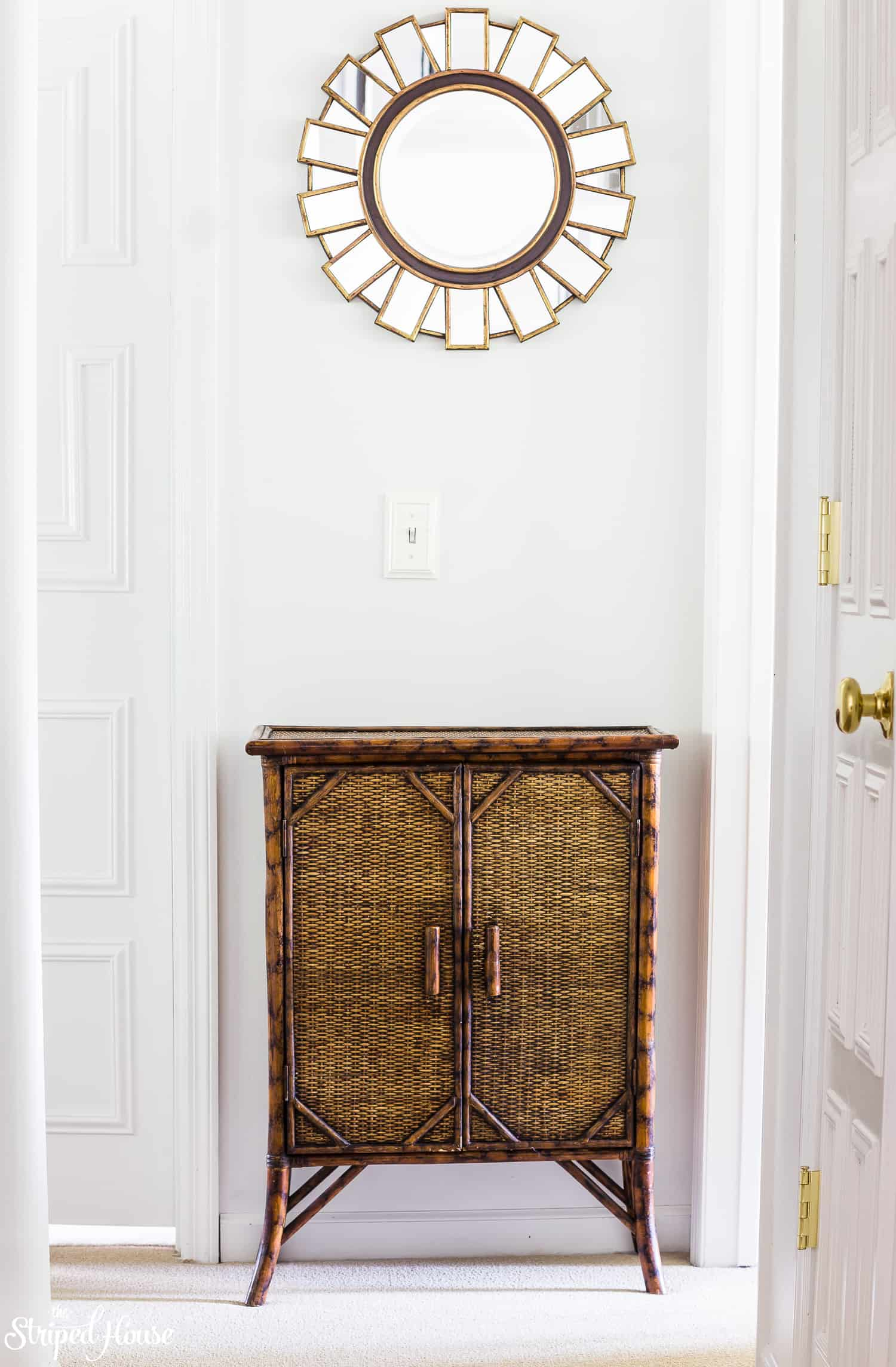 White neotraditional hallway with thrifted decor, bamboo console and gold starburst mirror.