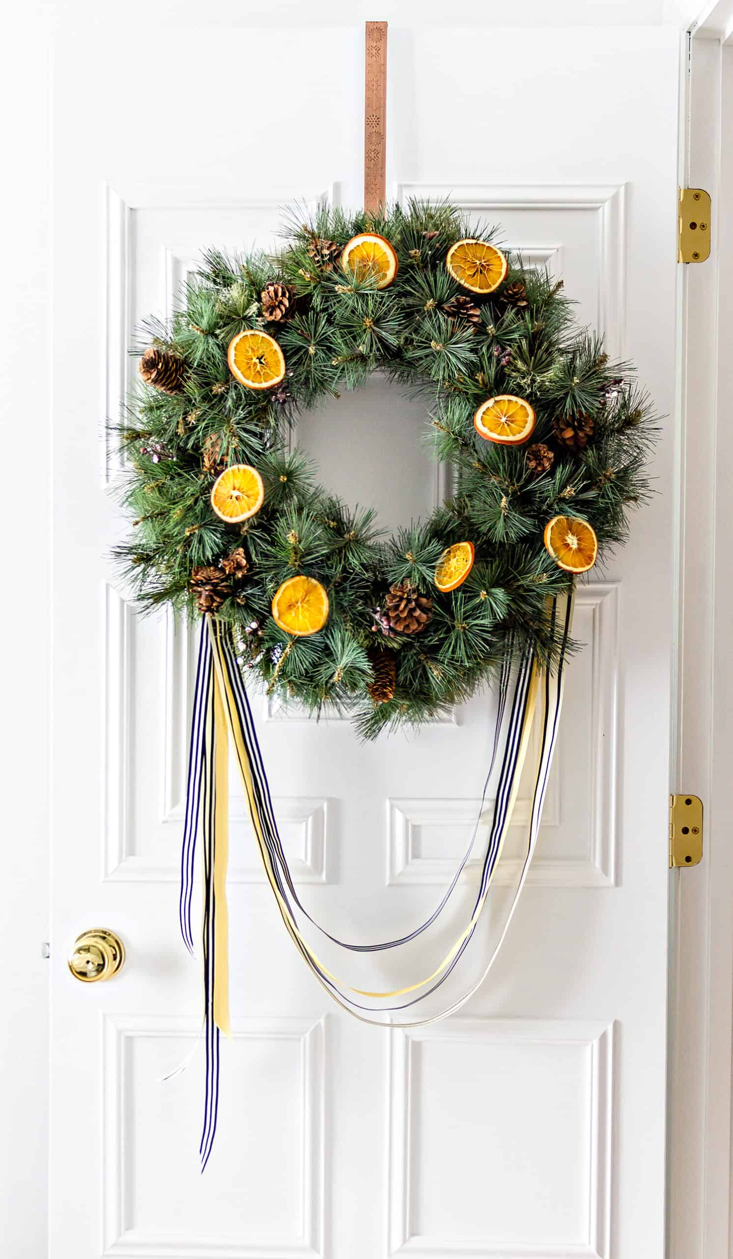Faux green wreath with dried orange slices and ribbon. How to bake orange slices to use in holiday decor.
